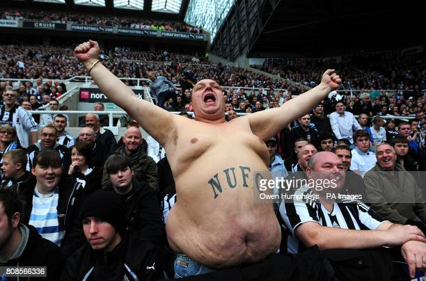 A bare chested Newcastle United fan celebrates in the stands