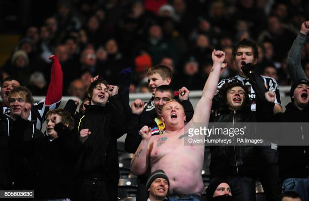 Bare chested Newcastle United fan cheers on his side in the stands