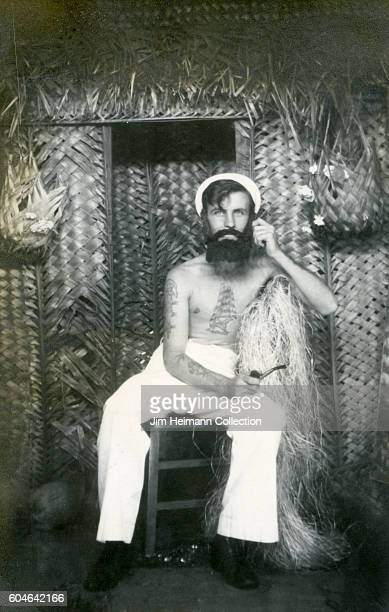 Bare chested sailor with tattoos and smoking pipe in front of straw hut.