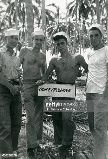 Bare chested sailors standing in back of cable crossing sign Tropical palm trees in background