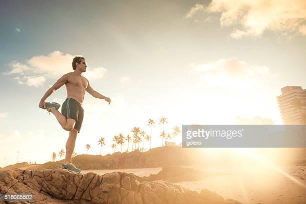 nackten oberkörper sportler macht gymnastik brasilianischen strand bei sonnenuntergang - chest barechested bare chested stock-fotos und bilder
