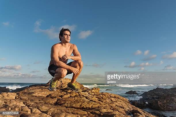 nackten oberkörper sportler sitzen auf klippen unter brasilianischen blauen himmel - chest barechested bare chested stock-fotos und bilder