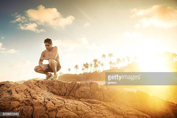 nackten oberkörper sportler sitzen auf klippen brasilianischen strand bei sonnenuntergang - chest barechested bare chested stock-fotos und bilder