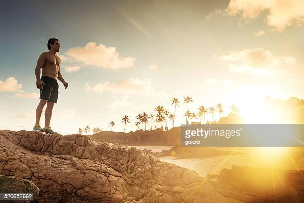 nackten oberkörper sportler stehen auf felsen bei sonnenuntergang brasilianischen strand - chest barechested bare chested stock-fotos und bilder