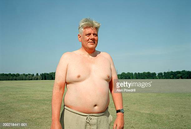 bare chested sunburnt man standing in field - chest barechested bare chested fotografías e imágenes de stock