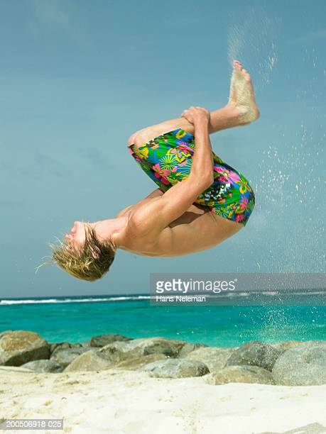 bare chested young man doing somersault in air - barechested bare chested ストックフォトと画像