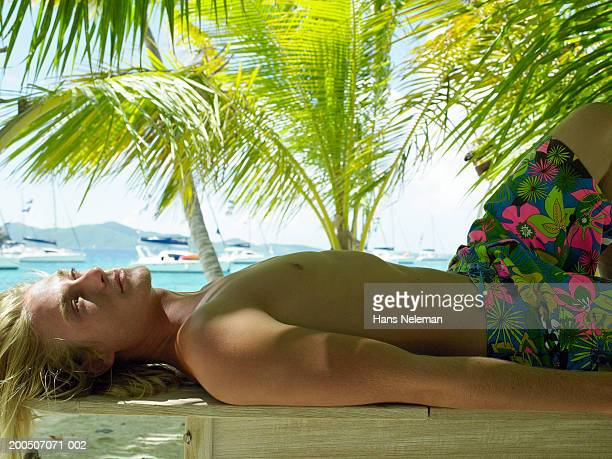 bare chested young man lying in shade by sea, side view - chest barechested bare chested stock-fotos und bilder