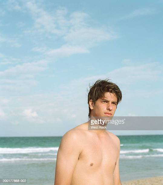 bare chested young man on beach - barechested bare chested ストックフォトと画像