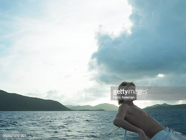 bare chested young man on boat, side view - chest barechested bare chested stock-fotos und bilder