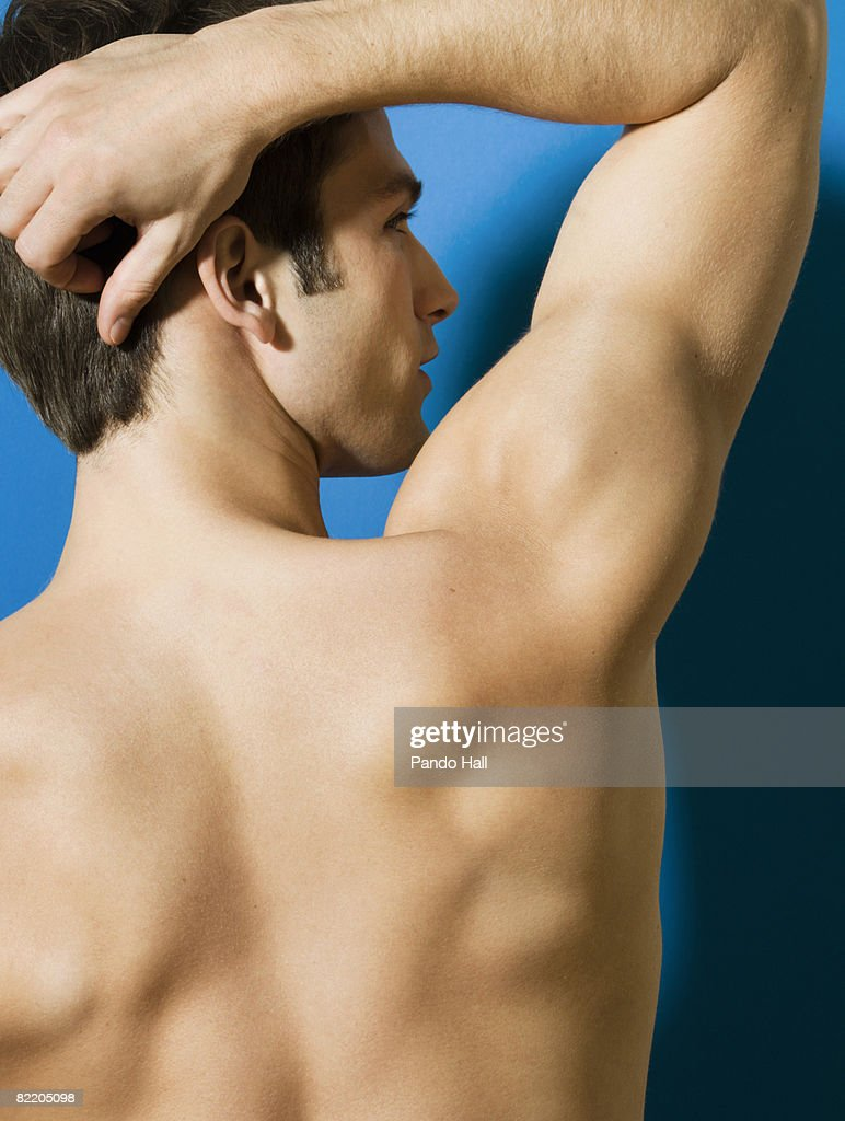 Bare chested young man, rear view : Stock Photo