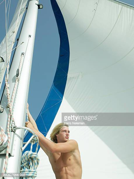 bare chested young man sailing yacht - chest barechested bare chested foto e immagini stock