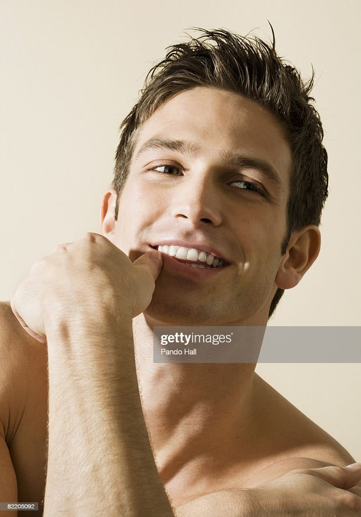 Bare chested young man, smiling, portrait  : Stock Photo