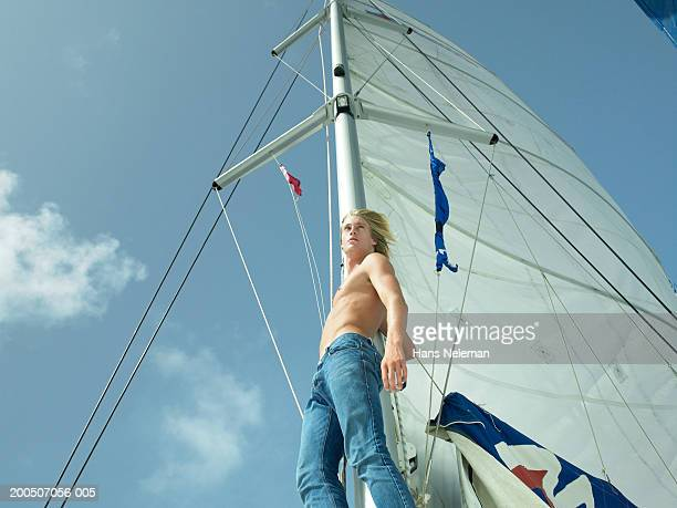 bare chested young man standing on yacht, low angle view - chest barechested bare chested stock-fotos und bilder