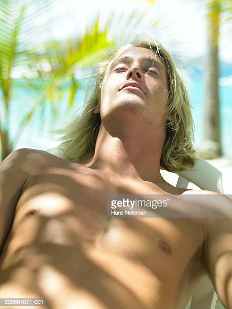 bare chested young man sunbathing, eyes closed - chest barechested bare chested stock-fotos und bilder