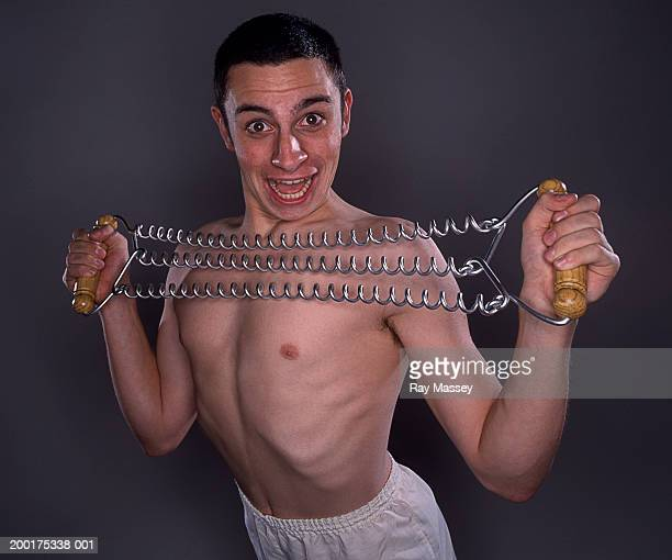bare chested young man using chest expander, smiling, portrait - barechested bare chested ストックフォトと画像