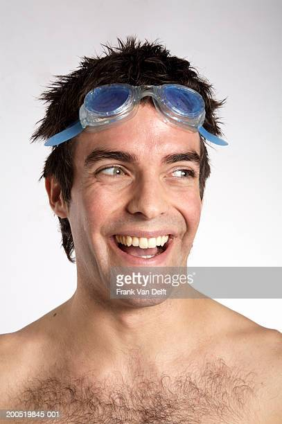 bare chested young man wearing swimming goggles, smiling, close-up - barechested bare chested ストックフォトと画像