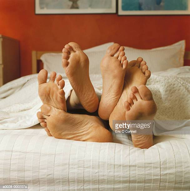 bare feet in bed - three people stock pictures, royalty-free photos & images