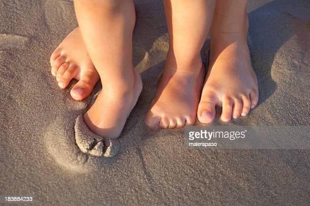 Bare feet in wet sand on beach