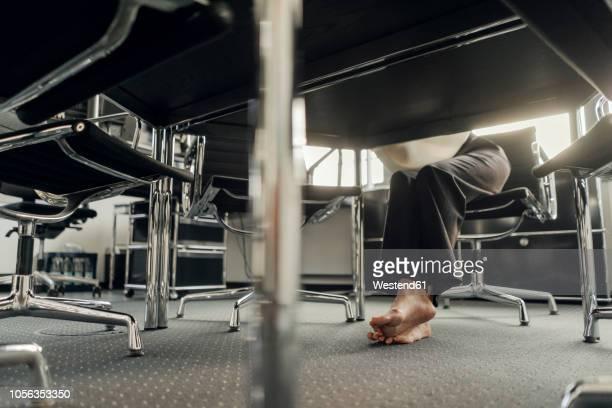 bare feet of businesswoman under her desk - goed gekleed stockfoto's en -beelden