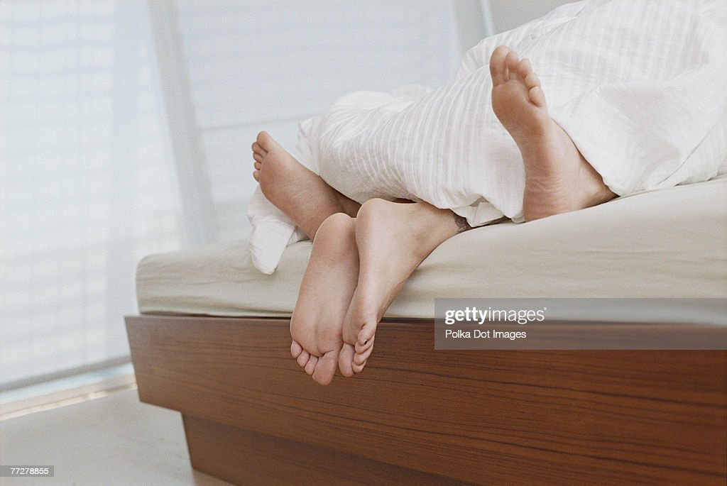 Bare feet of couple in bed : Stock Photo