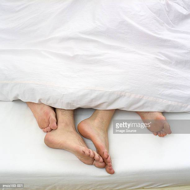 Bare feet of couple in bed