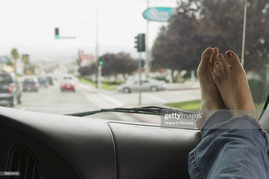 Bare feet on dashboard of car : Stock Photo