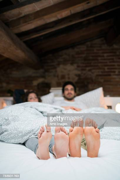 Bare feet soles of young couple lying in bed