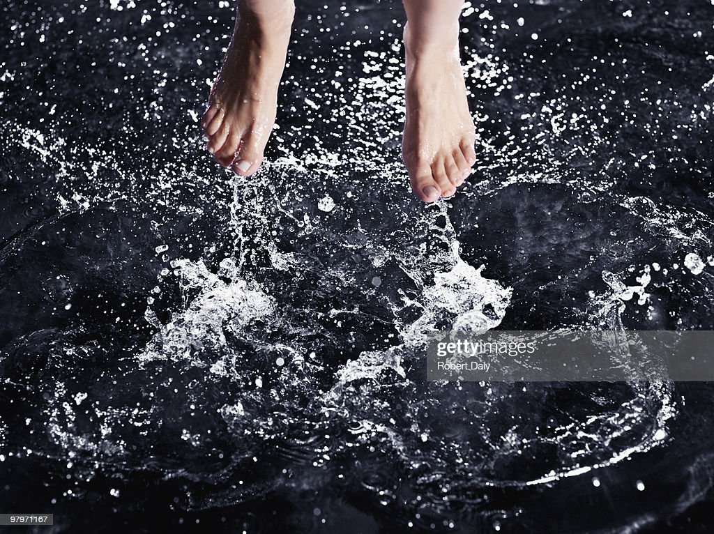Bare feet splashing in water : Stock Photo