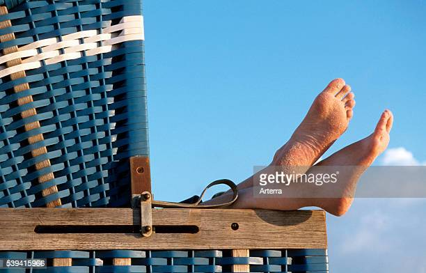 Bare feet sticking out from roofed wicker beach chair along the North Sea coast on the island Sylt Germany