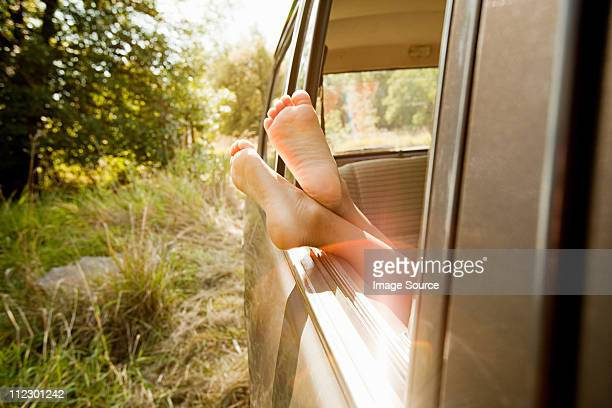 Bare feet sticking out of a car window