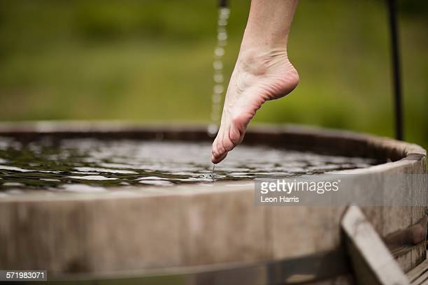 Bare foot of mature woman stepping into fresh cold water tub at eco retreat