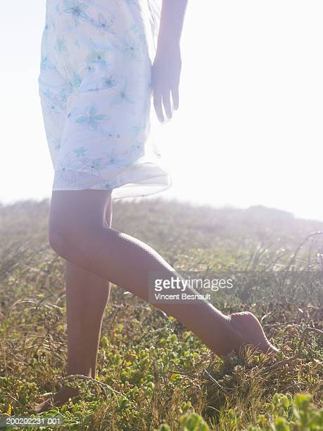 Bare footed teenage girl (14-16) on grass, low section (soft focus)
