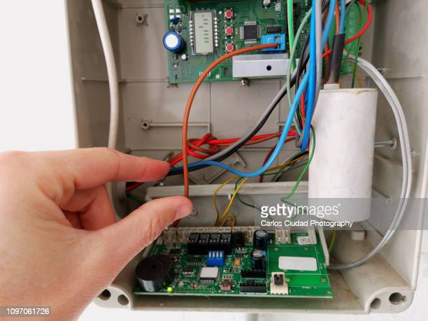 Bare human hand touching cables inside electrical panel