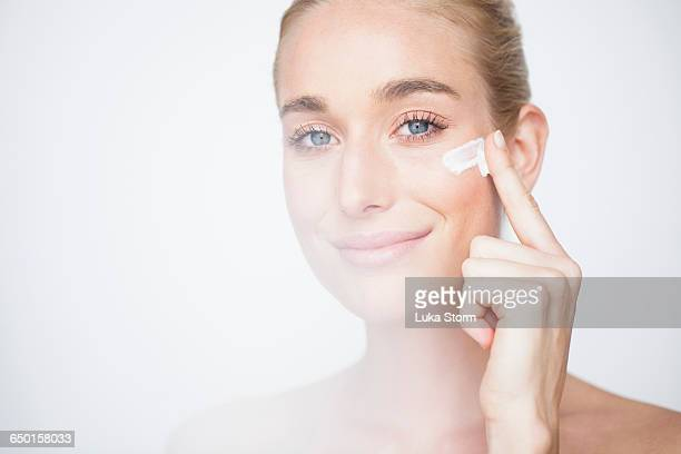Bare shouldered woman rubbing face cream into cheek looking at camera smiling