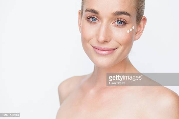 Bare shouldered woman with face cream on cheek looking at camera smiling