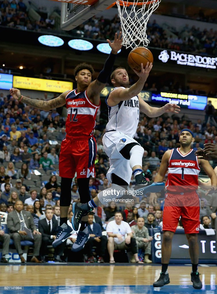J.J. Barea #5 of the Dallas Mavericks drives to the basket against Kelly Oubre Jr. #12 of the Washington Wizards and Jared Dudley #1 of the Washington Wizards in the first half at American Airlines Center on December 12, 2015 in Dallas, Texas.