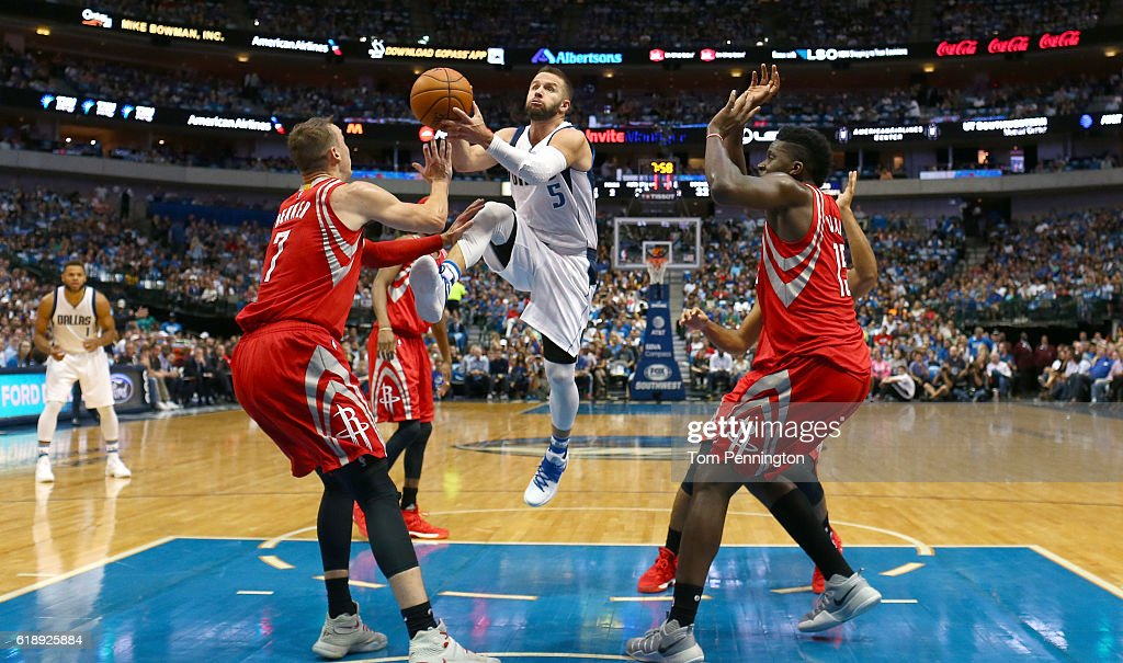J.J. Barea #5 of the Dallas Mavericks drives to the basket against Sam Dekker #7 of the Houston Rockets and Clint Capela #15 of the Houston Rockets in the first half at American Airlines Center on October 28, 2016 in Dallas, Texas.