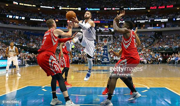 J Barea of the Dallas Mavericks drives to the basket against Sam Dekker of the Houston Rockets and Clint Capela of the Houston Rockets in the first...