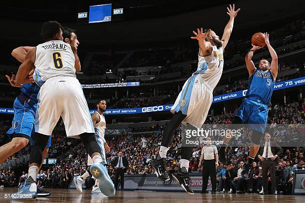 J Barea of the Dallas Mavericks takes a shot over Joffrey Lauvergne of the Denver Nuggets as Axel Toupane of the Denver Nuggets battles for...