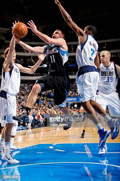 J Barea of the Minnesota Timberwolves drives to the basket against Rodrigue Beaubois and Dirk Nowitzki of the Dallas Mavericks on January 14 2013 at...