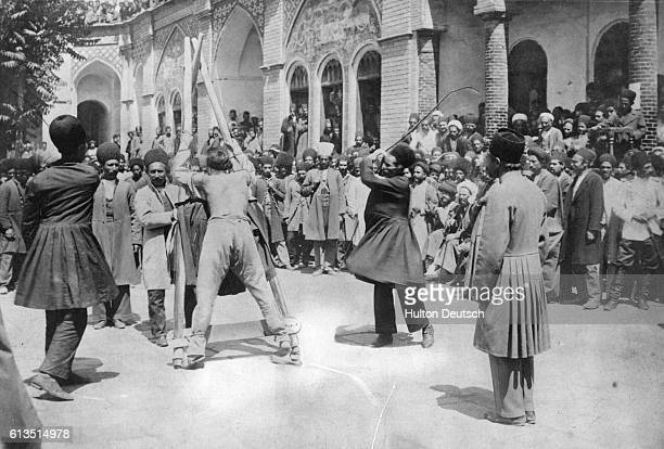 A barebacked man tied to a wooden stockade is publicly flogged in front of a crowd of men in a public square in Persia
