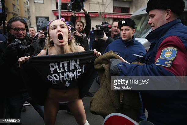 A barebreasted Femen protester demonstrates against the scheduled visit of Russian President Vladimir Putin moments before she was detained by police...