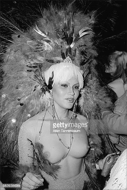 A barebreasted lady in a peacock feather headdress dances at Studio 54's first Halloween party New York New York October 31 1977