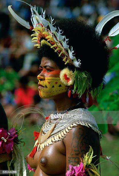 Barebreasted native woman wearing a feathered headdress beaded necklaces and face paints during a gathering of tribes at Mount Hagen in Papua New...