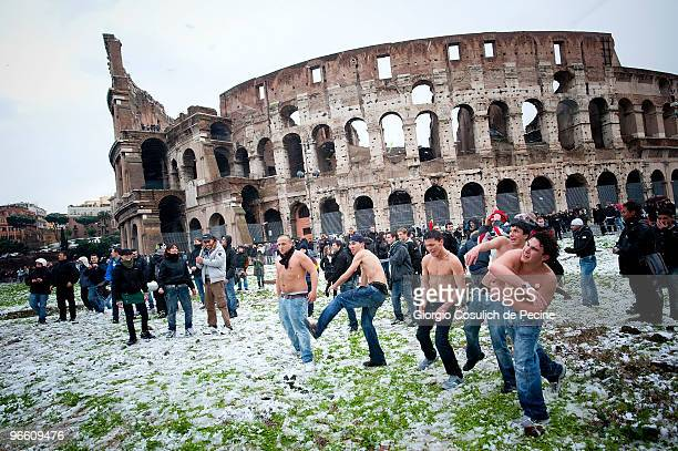 Barechest guys enjoy the snow in front of the Coliseum on February 12 2010 in Rome Italy Rome has seen today its heaviest snow since 1986