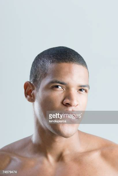 Bare-chested African man biting lip