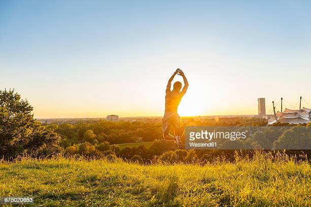 Barechested athlete jumping on meadow at sunset