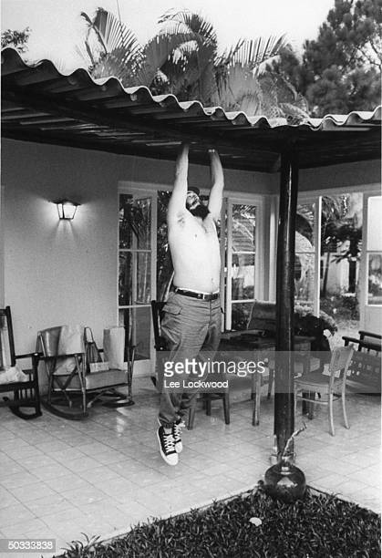 Barechested Fidel Castro on porch of his retreat on Isle of Pines attempting a chinup