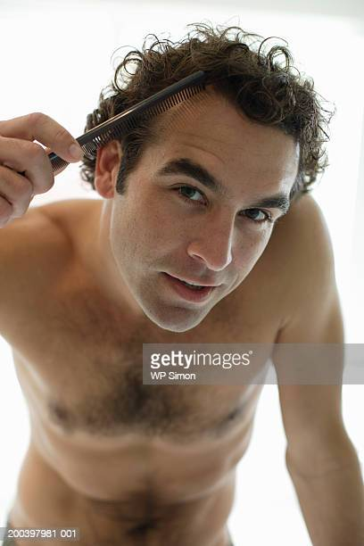 bare-chested man combing hair, portrait, close-up - barechested bare chested ストックフォトと画像
