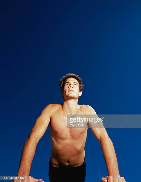 bare-chested man doing press-ups, outdoors, low angle view - chest barechested bare chested foto e immagini stock